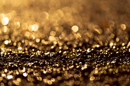 Sparkling light boke blur. Sea pebbles. Golden glitter particles background. Zdjęcie Seryjne