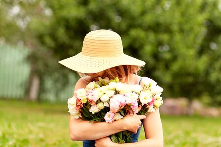 A young woman holds a large bouquet of peonies in front of her. In a straw hat with wide brim. Looks to the right. Sunny summer day. 版權商用圖片