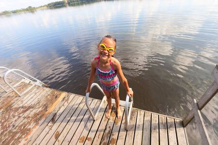 Smiling girl on the pier after swimming. In a swimming suit and swimming goggles. Against the background of the water surface of the lake with reflection of blue sky and white clouds. Sunny summer day
