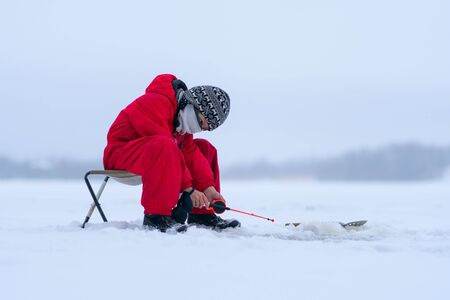 A boy in red overalls on a frozen snowy lake. Fishing rod in the hands of a boy. Looks into the hole. Winter fishing. Snowy forest on the horizon.
