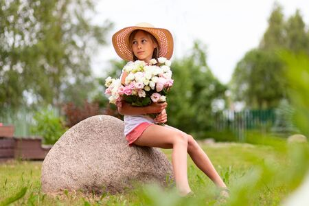 Girl holding a large bouquet of peonies. Young teenager in a hat with wide brim is sitting in a flowering meadow. Girl with two braids. Sunny summer day.