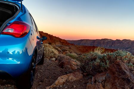 Close up view of blue car. Tourism car on off road with sunset landscape.