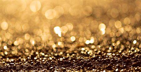 Sparkling light boke blur. Sea pebbles. Golden glitter particles background. Stock fotó
