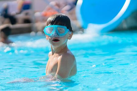 Boy in an outdoor pool at a tropical resort. Mastering the basics of scuba diving. A boy in water glasses in the pool. He listens carefully to the instructions of the coach.