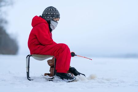 Little boy in red overalls on winter fishing. Sits on a folding chair. In the hands of a fishing rod. Looks into the distance. White snow. The skyline merges with the sky. Stock fotó