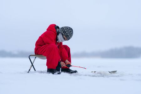 Little boy in red overalls on the lake. Winter fishing. Fishing rod in the hands of a boy. He bent down and carefully looks into the hole. White snow all around. Low clouds. Mainly cloudy. Stock fotó