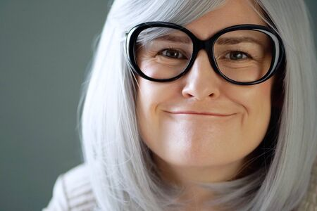Emotional portrait of a woman in big black glasses. The emotion of misunderstanding. Close-up. Gray background. Stock fotó