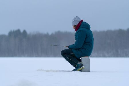 A man on a frozen snowy lake. Side view. Winter fishing. Fishing rod in the hands. Ice hole. White snow. Snow-covered forest and lake shore on the horizon. Grey sky.