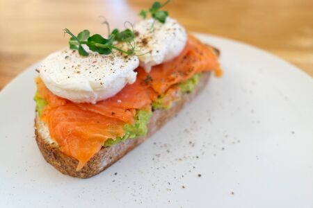 Healthy and nutritious food. Sandwich with fish: salmon, coarse-grained bread, cream cheese, guacomolly cheese, poached egg, avocado, greens. On a white plate. Stock fotó