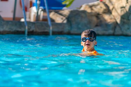 A happy boy in swimming goggles and arm ruffles in an outdoor pool. The child learns to swim. Family holidays at a tropical resort. Stock fotó