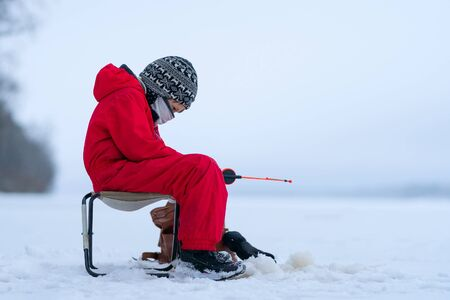 A boy in red overalls on winter fishing on the lake. Sits in an armchair near the hole. In the hands of a fishing rod. Looks carefully at the fishing rod. The horizon merges with the sky.