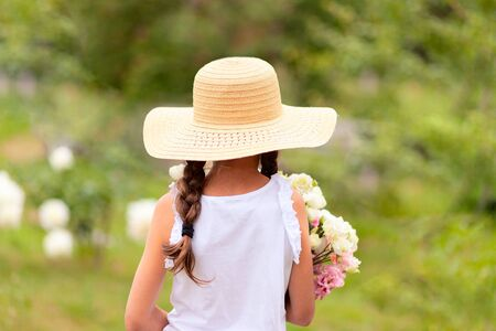 A girl with pigtails holds in her hands a bouquet of white and pink peonies. A child in a wide-brimmed straw hat on a sunny summer day. Green background. Back view.