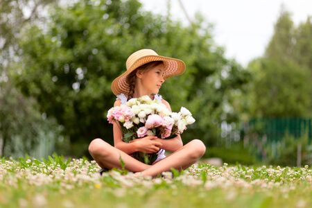 A bouquet of pink and white peonies in the hands of a girl sitting in a flowering meadow. A child in a straw hat with wide brim on a background of green trees. Sunny day.
