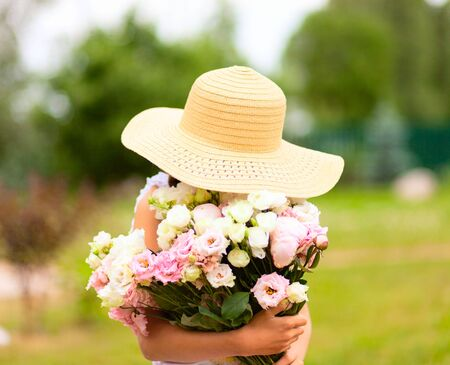 The girl holds a large bouquet of pink and white peonies in front of her. A child in a straw hat with wide brim. Enjoys the scent of flowers. Sunny summer day. Stock fotó
