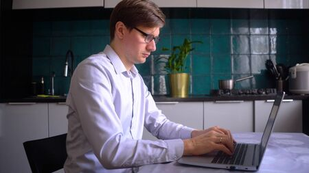 A man works in the kitchen at a laptop at home. Concept for remote work at home during the coronavirus quarantine period Covid 19.