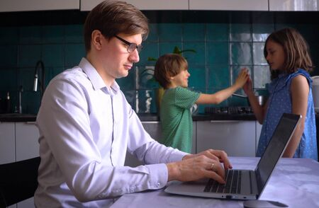 A man works in the kitchen at a laptop with his children at home. Father with son and daughter. Remote work at home during the coronavirus quarantine period Covid 19.