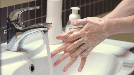 The right technique for good hand hygiene to protect yourself from the germs and the Covid19 coronavirus. Prolonged soaping, rubbing and washing off hands with water. Close up view. Stock fotó