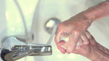 The concept of protecting the body from germs and viruses. Close up hands of senior man that applying lather and soap to make cleaning from germ, bacteria. Protect youself from infection Covid-19. Stock fotó