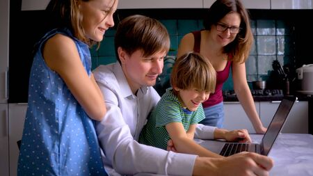 Stay home concept. Cute children use laptop for education, online study. Boy and Girl have homework at distance learning. Lifestyle concept for Family quarantine covid-19. Father helps son.