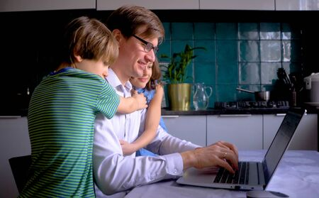 Remote home work during the quarantine period of the Covid 19 coronavirus, when the family is at home. A man works in the kitchen for a laptop. Father and children are smiling.