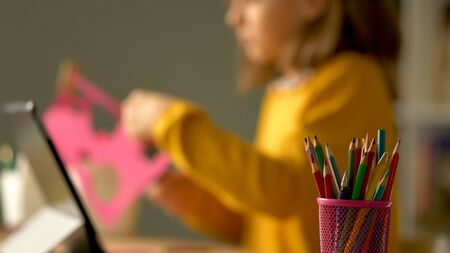 Distance education of children at home. A schoolgirl performs a creative task out of paper. In the foreground is a glass with colored pencils.