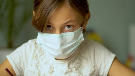 Home training during the quarantine period of the coronavirus Covid19. A girl in a medical protective mask do homework. Close up view.