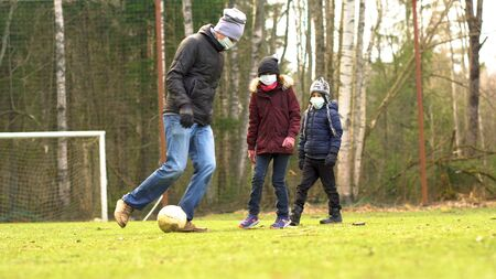 Family plays football on the playground during quarantine Covid-19. Father with children wearing medical face mask to protect from Corona Virus.