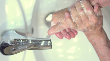 The concept of protecting the body from germs and viruses. Close up hands of senior man that applying lather and soap to make cleaning from germ, bacteria. Protect youself from infection Covid-19. 免版税图像