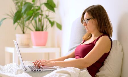 A woman works in the bedroom at a laptop.. Remote work at home during the coronavirus quarantine period Covid 19.