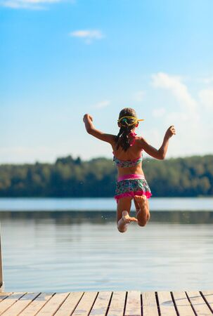 Young girl jumping into water, summer time