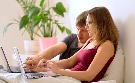 A man and woman work in the bedroom at a laptop.. Remote work at home during the coronavirus quarantine period Covid 19.