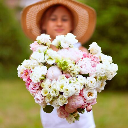 A wonderful large bouquet of white-pink peonies in the hands of a girl. A child in a straw hat with wide brim on a background of green vegetation. Sunny day. Stock fotó
