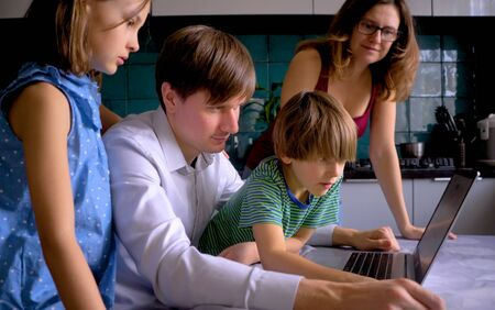 Cute children use laptop for education, online study. Boy and Girl have homework at distance learning. Lifestyle concept for Family quarantine covid-19. Father helps son.