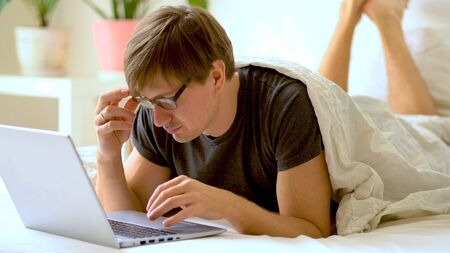 Young man with glasses is working from home during Coronavirus or Covid-19 quarantine. Man using laptop for work during self-isolation.