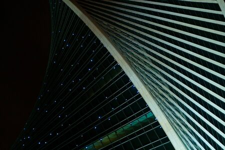 Modern urban architecture. Geometric pattern structure. Large panoramic windows. Beautiful night view of the skyscraper of the city of Moscow against the background of the black night sky. 免版税图像