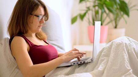 A young woman works in the bedroom at a laptop. Stay home concept. Remote work at home during the coronavirus quarantine period Covid 19.