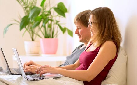 A young man and young woman work in the bedroom at a laptop. Stay home concept. Remote work at home during the coronavirus quarantine period Covid 19.