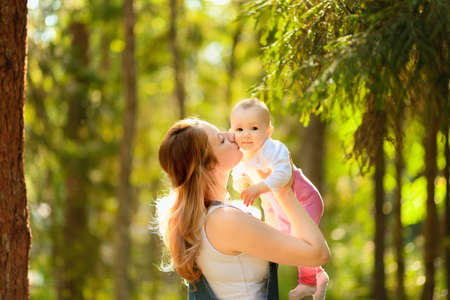 Young mother holding daughter in her arms. mom kisses and plays with daughter in the summer. Happy family in the park.