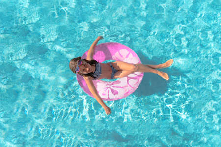 Happy girl in bikini in the swimming pool. Child on the inflatable mattress. Lovely teenager sunbathes and playing in blue water. Summer vacations.
