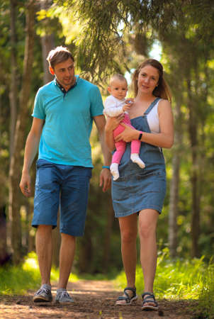 Mother, father and baby walking in the park. Summer time. Happy family spent time together outdoors. Woman holds his daughter in the arms.