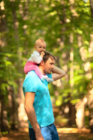 The child sits on his fathers shoulders. Father and baby walking in the park. Summer time. Happy family spent time together outdoors.