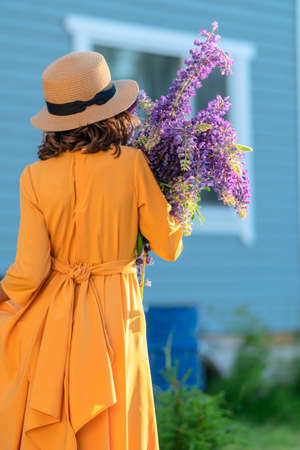 Girl in a straw hat hold a bouquet of lupine in her hands. Back view. 版權商用圖片