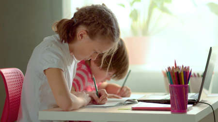 Cute children use laptop for education, online study, home studying, Boy and Girl have homework at distance learning. Lifestyle concept for home schooling.