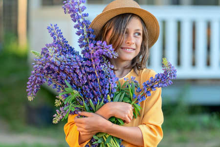 A smiling girl holds a beautiful big bouquet of lupine in her hands. A child in a straw hat. Sunny summer day.