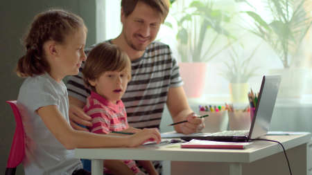 Cute children use laptop for education, online study, home studying, Boy and Girl have homework at distance learning. Lifestyle concept for home schooling. Father helps daughter and son.