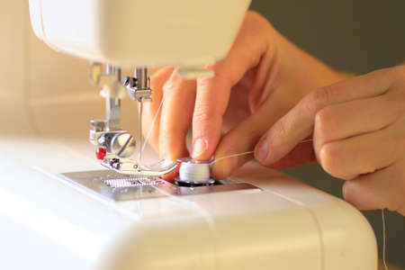 Preparing the sewing machine for work. Seamstress tucks thread into the eye of a needle. Installs the bobbin in the shuttle. Close up view. 版權商用圖片
