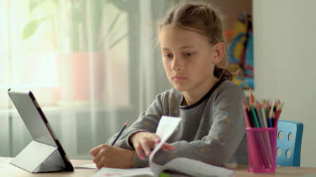 Cute children use laptop for education, online study, home studying, Girl has homework at distance learning. Lifestyle concept for home schooling.