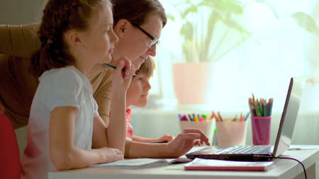 Cute children use laptop for education, online study, home studying, Boy and Girl have homework at distance learning. Lifestyle concept for home schooling. Mother helps daughter and son.
