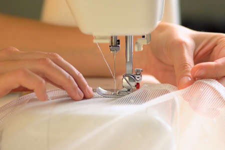 The process of sewing curtains from a mesh of white fabric. The rolled edge of the fabric is placed under the presser foot of the sewing machine. Close up view.