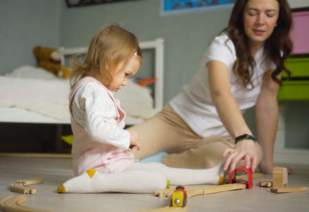 Mother and daughter playing together with construction toys indoor at home. Mom helps her baby girl. Family lifestyle concept.